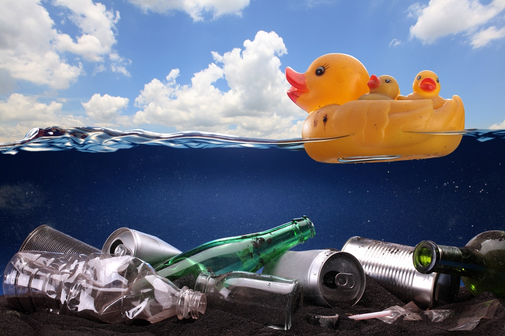 a plastic duck floating on a dirty water