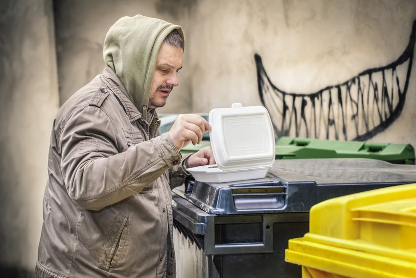 Homeless near garbage container with food box