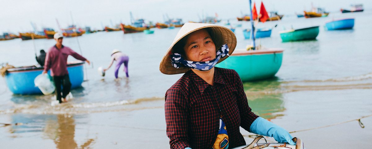 MUI NE, VIETNAM - 03 JANUARY, 2018: vietnamese woman holding aluminum bowl with fish and seafood on beach, Mui Ne, Vietnam